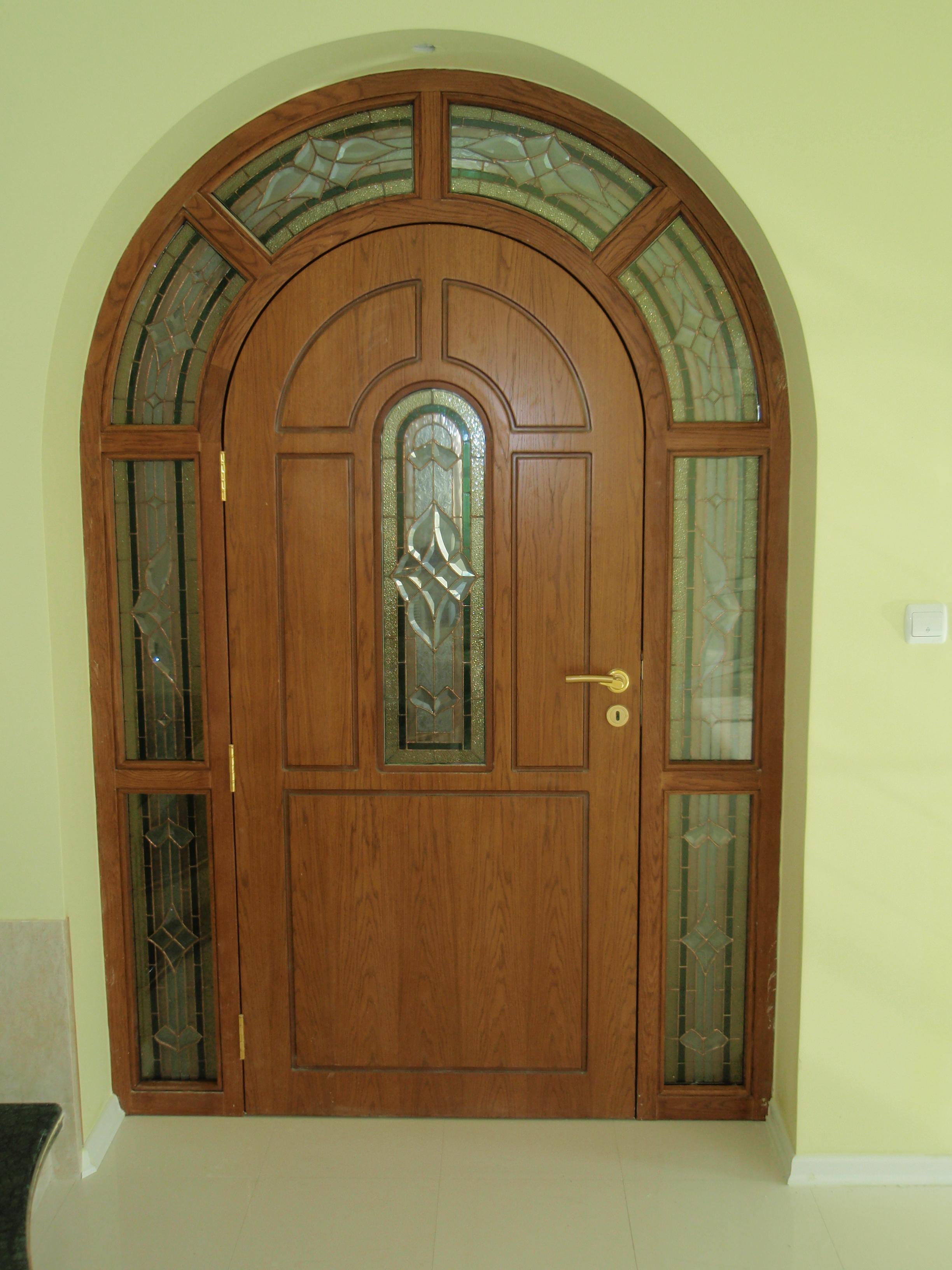 Масивна входна врата в нестандартен заоблен вид, декорирана с витражни стъкла